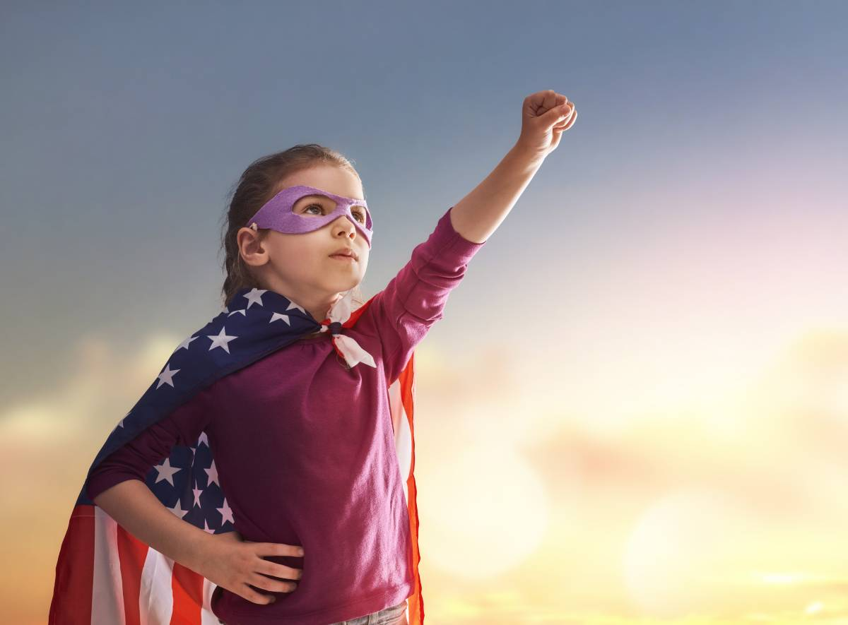 Child dressed up as superhero, wearing an American Flag cape with her hand in the air