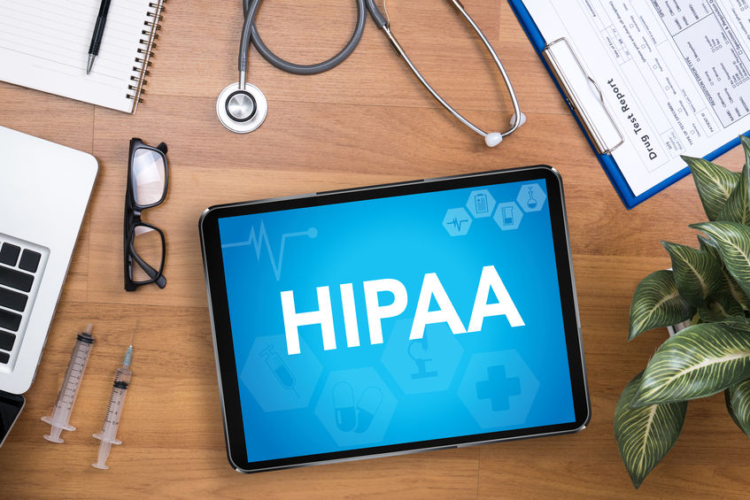 Tabletop with Medical Supplies and Tablet with HIPAA Lettering on Blue Backbground